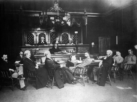 "Lewis Griffith McPhillips, seated at centre of ""The justices and officials of the Court of Appeal in a court room""; 1895, Vancouver City Archives, Port N863, http://searcharchives.vancouver.ca/justices-and-officials-of-court-of-appeal-in-court-room."