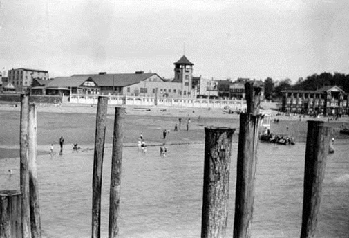 """Looking across English Bay beach to the """"Joy Wheel Fun Factory"""" [and] roller rink; VPL No 35445"""