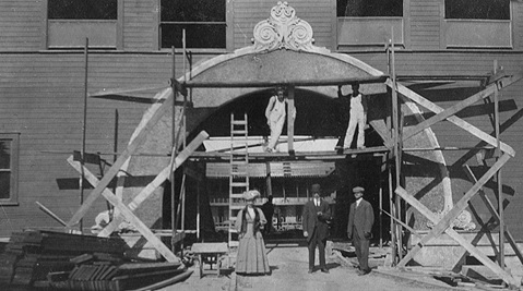 Vancouver Horse Show Building under construction; about 1909; source: family album of Helen G. White (Wilband), courtesy of D. Wilband. [people on ground in photograph tentatively identified as Bettie White, unknown person, Asa White.]