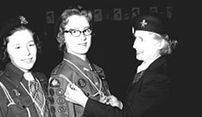 Girl Guides Barbara Shiels and Netannis King receiving their Gold Cords from Mrs. George F. Merrick, Prince George District Commissioner, March 24, 1959 [detail]; The Exploration Place, Settlers Effects, Catalogue ID: P991.9.2.256.6; http://www.settlerseffects.ca/pls/cats_web/WEB_EXHIBITIONS.show_image?ITEM_ID=328&LANG=EN&VRN=19
