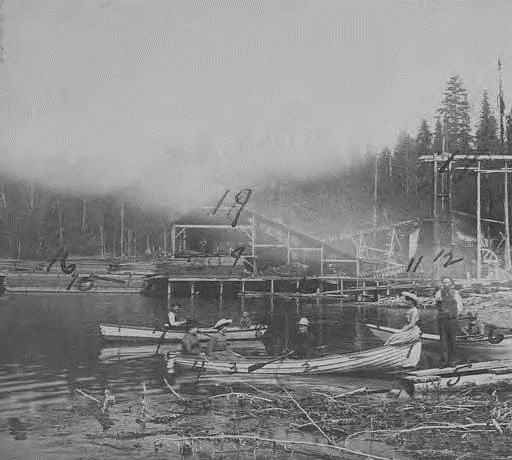 People at logging camp in Port Moody, British Columbia ; 1886; University of Washington Libraries; http://digitalcollections.lib.washington.edu/cdm/singleitem/collection/alaskawcanada/id/7098/rec/1: photographer: J.A. Brock, Vancouver City, B.C.; Written on verso: Partial view of the camp, Port Moody, British Columbia. [Numbered identifications correspond to numbers written on front of photo]: 1. Miss Melanie Dockrill; 2. C.T. Conover; 3. Miss Nellie Dockrill; 4. Mrs. Joseph Dockrill; 5. Joseph Dockrill; 6. Jos. S. MacDonald, timber inspector; 7. George McLacklan; 8. Frank Dockrill; 9. Henry Smith; 10. Jack Parks; 11. Hop Sing; 12. Will Harvey; 13. Cook house; 14. Office and C.T. Conover's room; 15. Scow loaded with lumber; 16. Commencement of wharf; 17. Flume and penstock; 18. China cabins; 19. End view of mill; 20. Susan Ericson. Dockrill's house and half a dozen cabins for the men do not show.