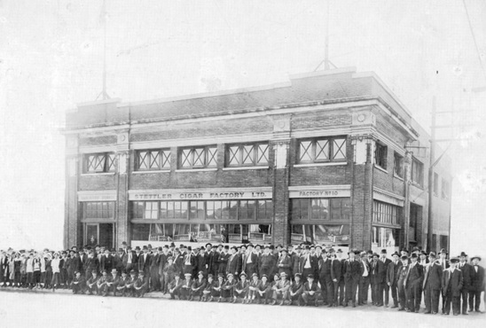 Stettler Cigar Factory, Vancouver Branch, Factory No. 10, at 418 West Georgia Street, 1917 or 1917; Vancouver City Archives, CVA 1376-336; https://searcharchives.vancouver.ca/group-in-front-of-stettler-cigar-factory-vancouver-branch-factory-no-10-at-418-west-georgia-street.