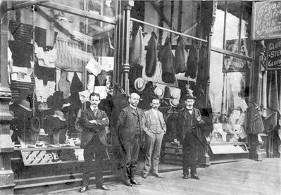 Exterior of Clubb and Stewart Mens' Furnishings (Klondike Outfitters) at 160 Cordova Street, 1898; Vancouver City Archives, CVA 371-878; https://searcharchives.vancouver.ca/exterior-of-clubb-and-stewart-mens-furnishings-klondyke-outfitters-at-160-cordova-street. [H.L.M. (Bert) Stewart, Mr. William Clubb, Mr. Angus Stewart and an unidentified man.]