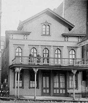 """Angel Hotel, 1870s, detail from """"Lion Hotel on the right, Angel Hotel on the left, Langley Street off Yates Street, Victoria""""; British Columbia Archives; Item A-09189; https://search-bcarchives.royalbcmuseum.bc.ca/lion-hotel-on-right-angel-hotel-on-left-langley-street-off-yates-street-victoria."""