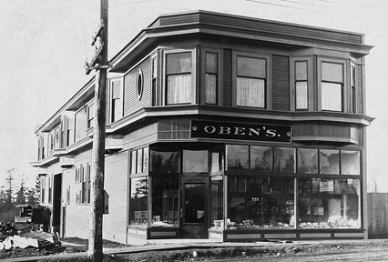 Oben's Vancouver, ancestry.ca, linked to John Oben. (Annotations on some versions of this photograph place the building at 413 Hastings Street. The actual location is the northwest corner of Fourth Avenue and Park Drive, later called Commercial Drive.)