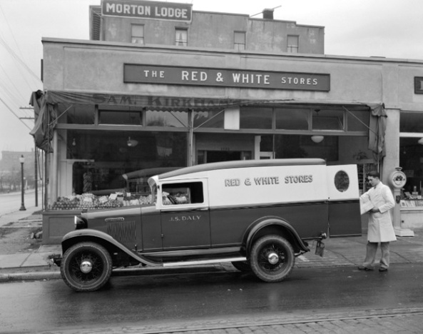 Red and White truck being loaded in front of a Red and White Store on Morton Street [Avenue], October 24, 1933; Vancouver City Archives; CVA 99-4562; https://searcharchives.vancouver.ca/red-and-white-truck-being-loaded-in-front-of-red-and-white-store-on-morton-street. [Northwest corner of Denman Street and Morton Avenue, looking west. Name on store is Sam Kirkham (1886-1979). Name on truck is J.S. Daly: Jervoice Sydney Daly (1884-1967).]