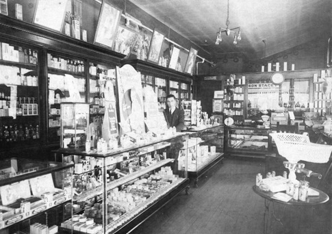 "Interior of Burrard Pharmacy, about 1924, Vancouver City Archives, CVA 1376-194; https://searcharchives.vancouver.ca/interior-of-burrard-pharmacy photograph shows shop assistant Mr. Davis behind the counter. Written on the back: ""Burrard Pharmacy, proprietor Wilson Stacey, interior view showing employee."""